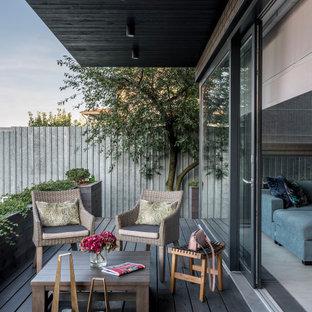 Свежая идея для дизайна: веранда в современном стиле с настилом и навесом - отличное фото интерьера