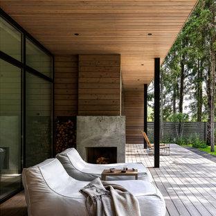 Свежая идея для дизайна: веранда среднего размера на заднем дворе в современном стиле с уличным камином, настилом и навесом - отличное фото интерьера