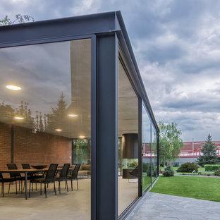 Foto di un piccolo portico industriale nel cortile laterale con pavimentazioni in pietra naturale e un tetto a sbalzo