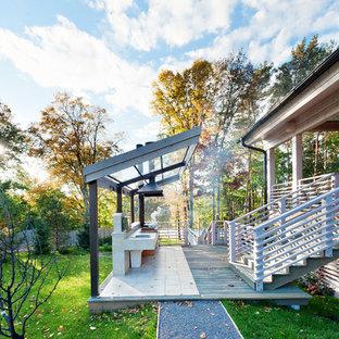 Inspiration pour un porche avec une cuisine extérieure design avec une pergola.