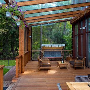 Свежая идея для дизайна: большая веранда на переднем дворе в современном стиле с навесом, крыльцом с защитной сеткой, покрытием из каменной брусчатки и деревянными перилами - отличное фото интерьера