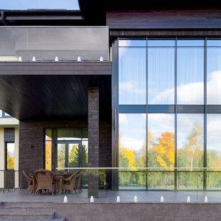 Idee per un grande portico nordico dietro casa con pavimentazioni in pietra naturale, un parasole e parapetto in vetro