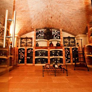 Cette image montre une grand cave à vin traditionnelle avec un sol en carreau de terre cuite et des casiers.