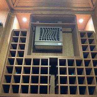 Cette image montre une petit cave à vin traditionnelle avec un sol en bois peint et des casiers.