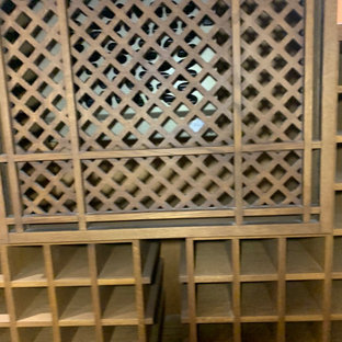 Cette photo montre une petit cave à vin chic avec un sol en bois peint et des casiers.