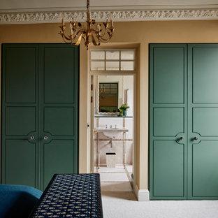 ウィルトシャーのトラディショナルスタイルのおしゃれな壁面クローゼット (フラットパネル扉のキャビネット、緑のキャビネット、カーペット敷き、グレーの床) の写真