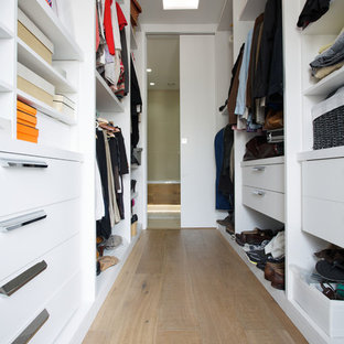 Trendy gender-neutral medium tone wood floor closet photo in London with flat-panel cabinets and white cabinets