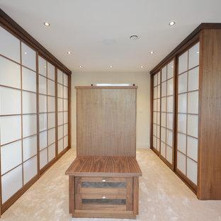 Foto di un grande spazio per vestirsi unisex moderno con ante lisce, ante marroni, pavimento in laminato e pavimento beige