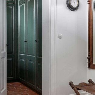 Ejemplo de armario vestidor pequeño con puertas de armario verdes, suelo de ladrillo y suelo rojo