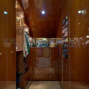 Foto de armario vestidor de hombre, marinero, de tamaño medio, con armarios con paneles lisos, puertas de armario de madera oscura y suelo de madera en tonos medios