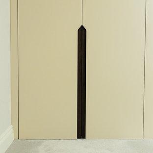 Modelo de vestidor unisex, actual, grande, con armarios con paneles lisos, puertas de armario beige y moqueta