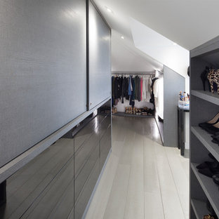 Design ideas for a large contemporary gender neutral dressing room in London with grey cabinets, open cabinets, light hardwood flooring and beige floors.