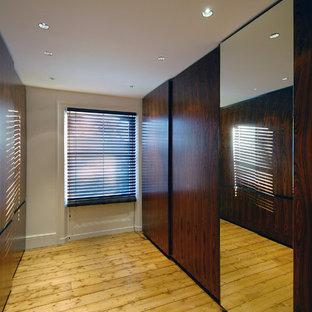 Ispirazione per una grande cabina armadio unisex design con ante lisce, ante in legno bruno e parquet chiaro