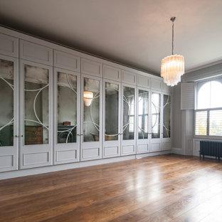 Foto de armario y vestidor ecléctico, extra grande, con puertas de armario blancas y suelo de madera en tonos medios
