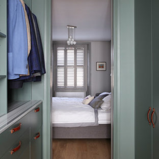 This is an example of a mid-sized modern men's walk-in wardrobe in London with flat-panel cabinets, green cabinets, medium hardwood floors and brown floor.