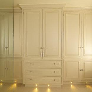 Imagen de armario y vestidor unisex, actual, grande, con armarios con paneles con relieve, puertas de armario verdes y suelo de piedra caliza