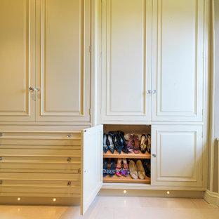 Aménagement d'un grand placard dressing classique neutre avec un placard avec porte à panneau surélevé, un sol en calcaire et des portes de placard jaunes.