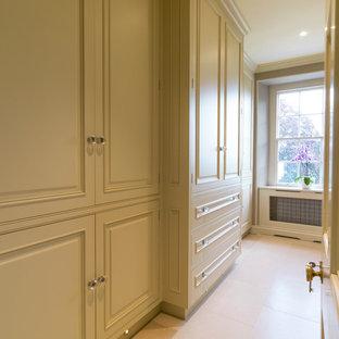 Foto de armario y vestidor clásico, grande, con armarios con paneles con relieve, puertas de armario verdes y suelo de piedra caliza