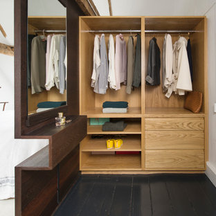 Inspiration for a mid-sized contemporary gender-neutral dressing room in Sussex with painted wood floors, black floor, open cabinets and light wood cabinets.