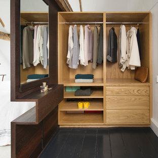Ejemplo de vestidor unisex, actual, de tamaño medio, con suelo de madera pintada, suelo negro, armarios abiertos y puertas de armario de madera clara
