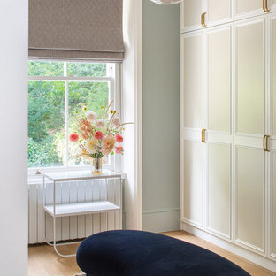 Inspiration for a classic walk-in wardrobe for women in London with recessed-panel cabinets, beige cabinets, medium hardwood flooring and brown floors.