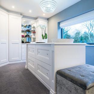 Immagine di una cabina armadio unisex tradizionale di medie dimensioni con ante bianche, moquette, pavimento grigio e ante con riquadro incassato