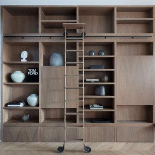 Cette photo montre un placard dressing nature de taille moyenne et neutre avec un placard sans porte, des portes de placard en bois brun, un sol en bois clair, un sol marron et un plafond à caissons.