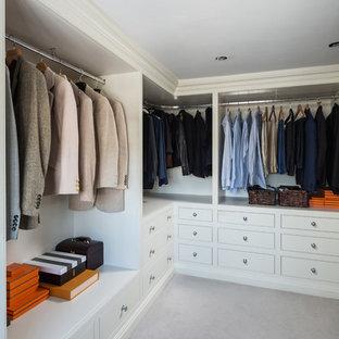 Immagine di un piccolo spazio per vestirsi unisex chic con ante a filo e moquette