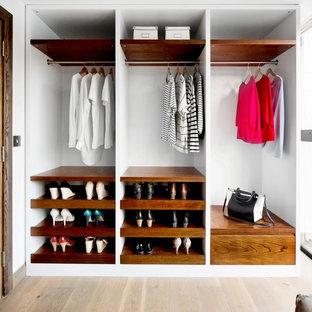 Idee per una cabina armadio unisex minimal di medie dimensioni con ante in legno scuro, parquet chiaro, pavimento beige e nessun'anta