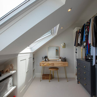 ロンドンの中くらいの男女兼用トランジショナルスタイルのおしゃれなウォークインクローゼット (カーペット敷き、グレーの床、シェーカースタイル扉のキャビネット、白いキャビネット) の写真