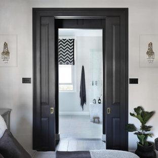 Ejemplo de armario vestidor unisex y casetón, actual, grande, con armarios abiertos, puertas de armario negras, suelo de contrachapado y suelo marrón