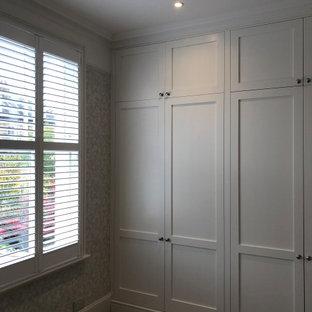 Geräumiges Klassisches Ankleidezimmer mit Einbauschrank, Schrankfronten mit vertiefter Füllung, weißen Schränken, Teppichboden und beigem Boden in London