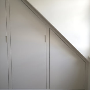 Esempio di un ampio armadio incassato vittoriano con ante lisce, ante bianche, moquette e pavimento beige