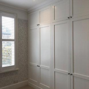 Ispirazione per un ampio armadio incassato vittoriano con ante con riquadro incassato, ante bianche, moquette e pavimento beige