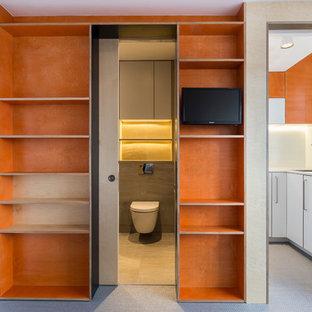 Kleines Modernes Ankleidezimmer mit flächenbündigen Schrankfronten, hellbraunen Holzschränken und Vinylboden in London