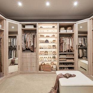 Foto di una grande cabina armadio minimal con ante lisce, ante in legno chiaro, pavimento beige e moquette