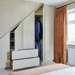 Imagen de armario tradicional renovado, de tamaño medio, con moqueta, armarios con paneles lisos, puertas de armario beige y suelo beige