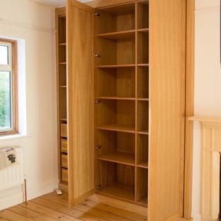 Immagine di un armadio o armadio a muro unisex minimal con ante con riquadro incassato e ante in legno chiaro