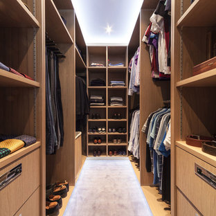 Inspiration for a contemporary walk-in wardrobe for men in London with open cabinets, medium wood cabinets, carpet and grey floors.