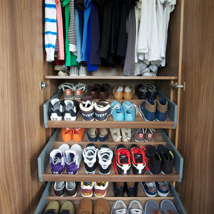 Inspiration for a small contemporary men's reach-in closet remodel in London with medium tone wood cabinets