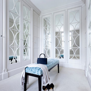 Medium sized classic walk-in wardrobe for women in Cheshire with white cabinets, carpet and white floors.
