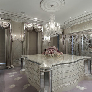 Expansive transitional women's dressing room with glass-front cabinets, light wood cabinets, carpet and multi-coloured floor.