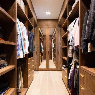 Imagen de vestidor unisex, actual, de tamaño medio, con armarios con paneles lisos, puertas de armario de madera oscura y suelo de madera clara
