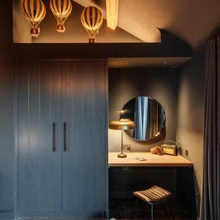 コーンウォールのコンテンポラリースタイルのおしゃれなフィッティングルーム (フラットパネル扉のキャビネット、グレーのキャビネット、濃色無垢フローリング、茶色い床、三角天井) の写真