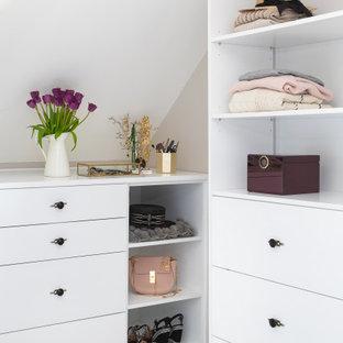 Immagine di uno spazio per vestirsi per donna contemporaneo di medie dimensioni con nessun'anta, ante bianche, moquette e pavimento beige
