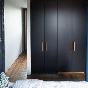 Cette image montre un grand placard dressing design neutre avec un sol en bambou, un placard à porte plane et des portes de placard noires.