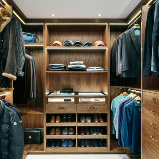 Inspiration for a medium sized contemporary walk-in wardrobe for men in Essex with flat-panel cabinets, medium wood cabinets, white floors and carpet.