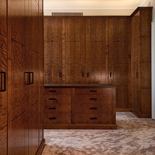 Photo of a contemporary dressing room in London with flat-panel cabinets, dark wood cabinets and carpet.