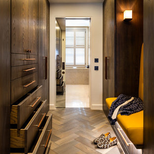 Inspiration for a medium sized contemporary gender neutral dressing room in London with flat-panel cabinets, dark wood cabinets and medium hardwood flooring.