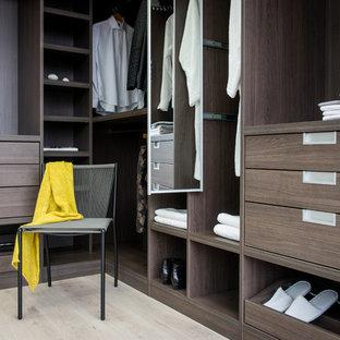 Imagen de armario vestidor unisex, contemporáneo, con armarios abiertos, puertas de armario de madera en tonos medios y suelo de madera clara